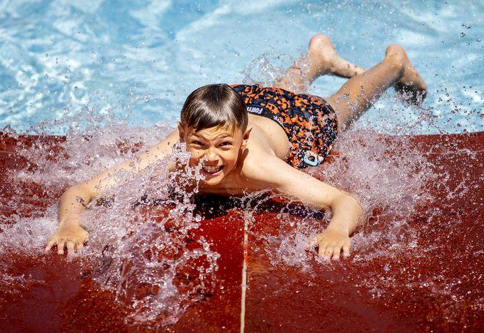 Zwemmers zoeken verkoeling in openluchtzwembad De Bever, op een tropisch warme dag.
