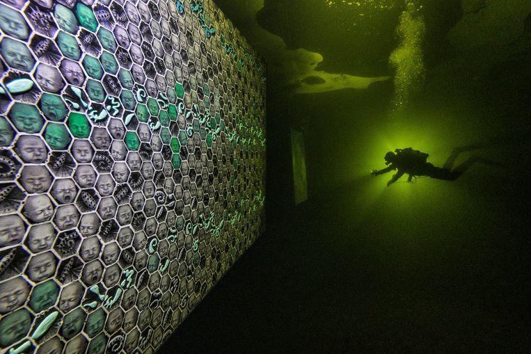 Onder het ijs in de Witte Zee bij de noordelijke Russische regio Karelië zijn kunstwerken geplaatst van onder anderen Denis Lotarev en fotograaf Viktor Lyagusjkin. De installaties zijn alleen te bekijken door duikers, van wie er hier een met een lamp op weg is naar een van de werken. De onderwaterkunst blijft daar tot het ijs is gesmolten. Beeld REUTERS