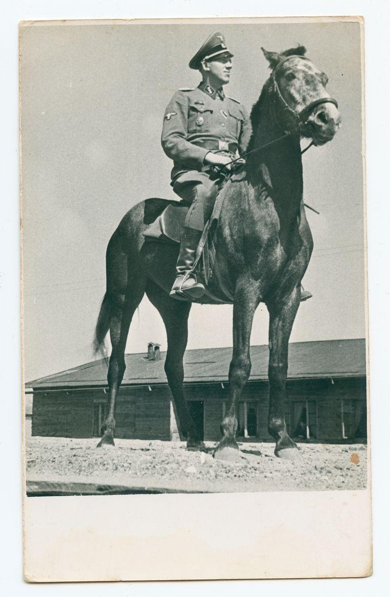Johann Niemann te paard, op het terrein waar de mensen die uit de deportatietreinen kwamen werden verzameld. Op de achtergrond: barakken voor hulpbewakers. Beeld United States Holocaust Memorial Museum