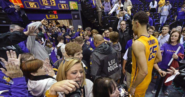 Simmons baant zich een weg tussen de fans. Beeld AP