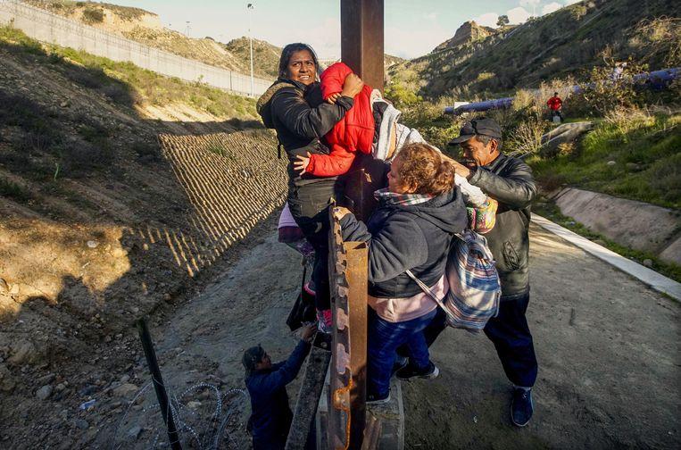 Hondurese migranten klimmen over het hek bij de Amerikaans-Mexicaanse grens in de buurt van Tijuana op 6 januari.  Beeld AFP