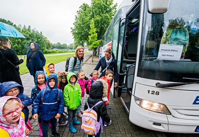 Kinderen gaan op schoolreisje, de ouders zwaaien hen uit.