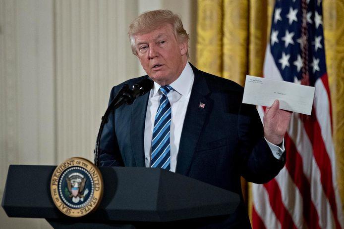 Trump met de brief die hij van Barack Obama kreeg.