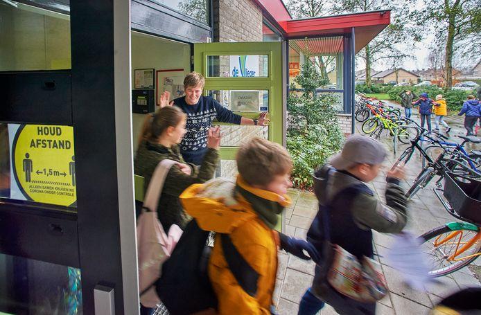 Juf Femke Raijmakers zwaait op 15 december 2020 de kinderen van groep 7 uit bij basisschool De Vlieger in Volkel.  Ze gaan voor vijf weken naar huis vanwege de nieuwe coronamaatregelen.