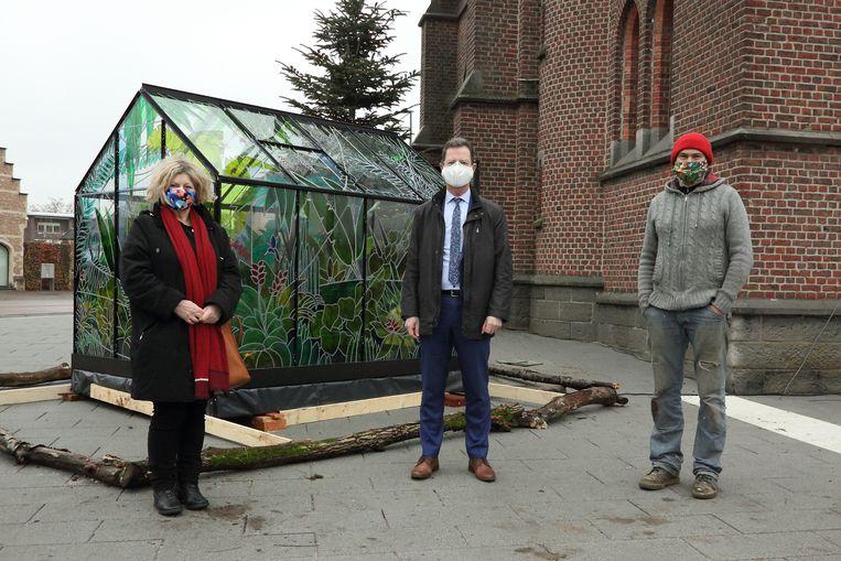 Schepenen Denise Vandevoort (sp.a) en Dirk Vansina (CD&V) samen met kunstenaar Pieter Janssens bij de kerststal in Wilsele. Beeld Stad Leuven