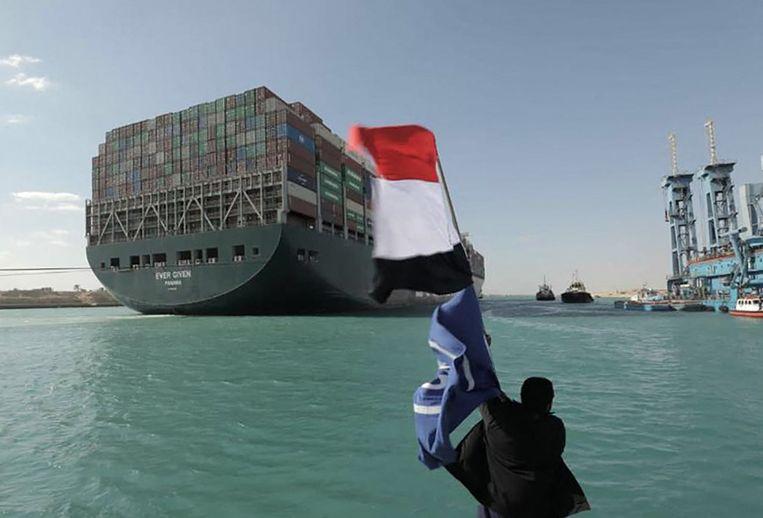 Een man wappert met de Egyptische vlag na het vlot trekken van de Ever Given in het Suez-kanaal. Beeld AFP