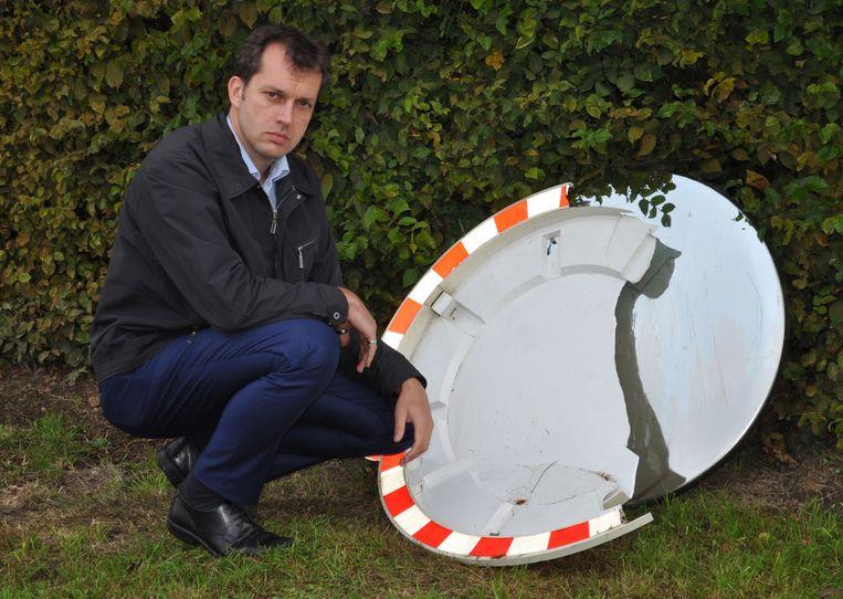 Kristof Meerschaut toont de schade: zo werd op de hoek van de Pruimelstraat en Ooikestraat de spiegel kapot gereden.