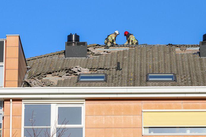 Brandweerlieden zijn bezig de dakpannen van de flat te halen.