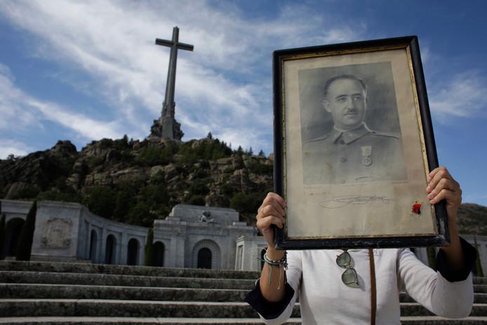 Een bezoeker houdt een portret omhoog van oud-dictator Francisco Franco.