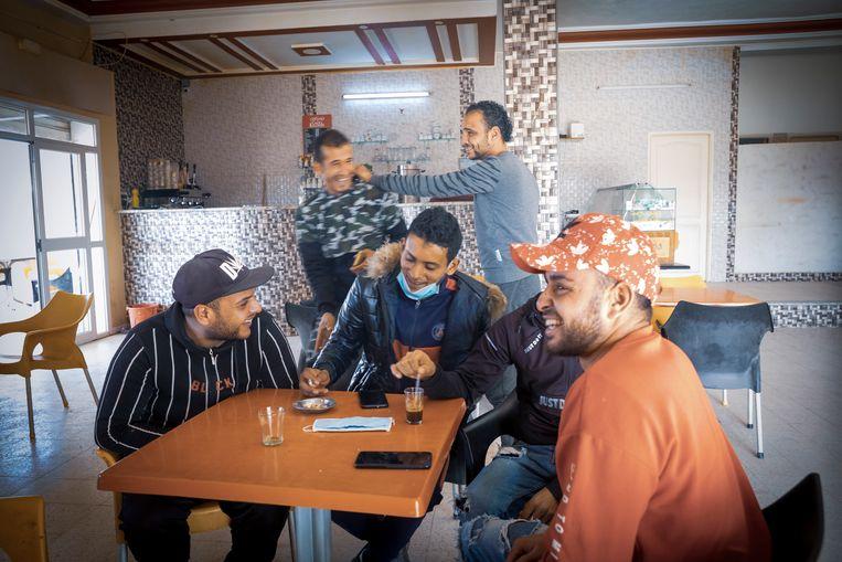 Werkloze jongeren in een buurtcafé in de Tunesische kustplaats Sfax. Rechts, met oranje pet, de 25-jarige Ahmed. 'We willen allemaal naar Europa.' Beeld Sven Torfinn