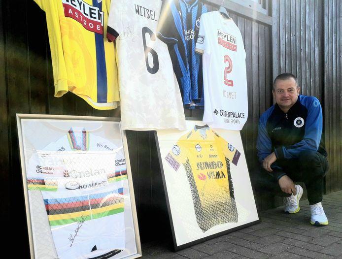 Willy's trainer Mike bij enkele van de shirts die geveild worden om de kleine voetballer te steunen in zijn strijd tegen leukemie