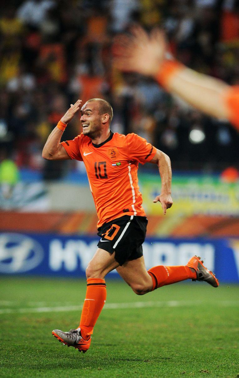 Wesley Sneijder, een van de kleinste spelers van het Nederlands elftal, wijst op zijn voorhoofd nadat hij met een kopbal de 2-1 heeft gemaakt tegen Brazilië. Beeld Guus Dubbelman