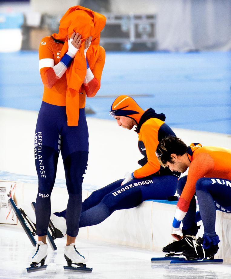 Kai Verbij trekt zijn veters los na zijn - zou later blijken - winnende 1.000 meter. Krol, hoofd verborgen in zijn jack, kan niet geloven dat hij zojuist zijn kansen vergooide met twee valse starts. Beeld Klaas Jan van der Weij / de Volkskrant