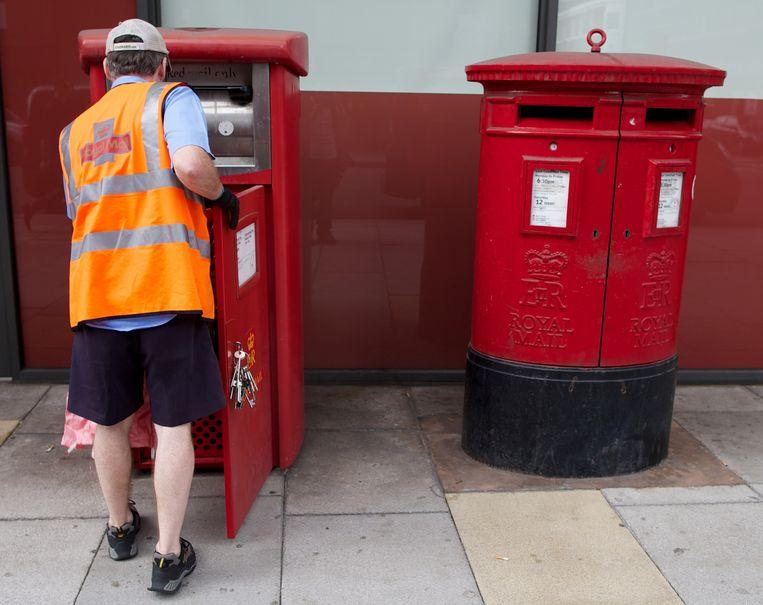 Een postbode haalt een brievenbus leeg in Londen. Archiefbeeld. Beeld AFP