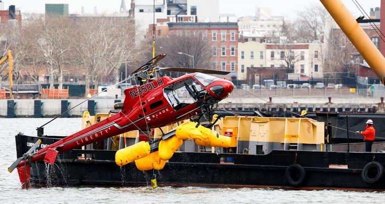 De helikopter die zondag in de East River in New York crashte, wordt uit het water gehesen.