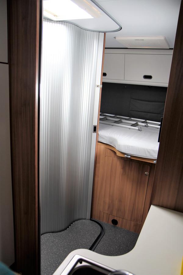Duidelijk zichtbaar op de vloer: de rails waarin de lamellendeur zich beweegt. Hij kan hierdoor verschillende posities innemen, zodat je kan kiezen voor óf ruimte in de badkamer óf een bredere doorgang tussen keuken en badkamer