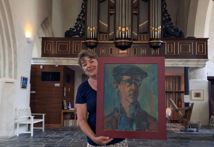 Sophie Schrameijer met het zelfportret van haar vader in het kerkje van Groede.