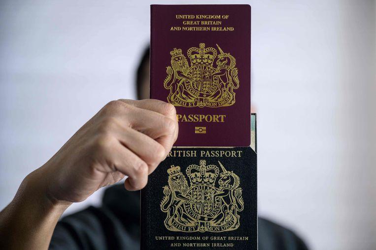 Een man uit Hongkong die al Brits staatsburger is, toont zijn oude en nieuwe (boven) paspoort. Beeld AFP