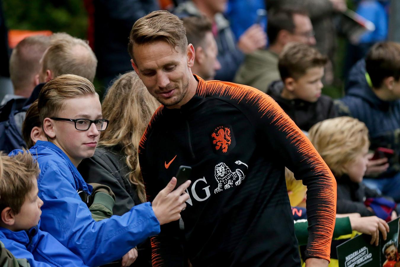 Luuk de Jong gaat na de training van Oranje op de foto met een fan.