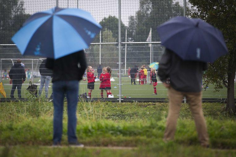 Ouders langs het veld bij voetbalvereniging VOC. De KNVB hoopt dat het autoverkeer richting de velden aan banden kan worden gelegd.  Beeld ANP