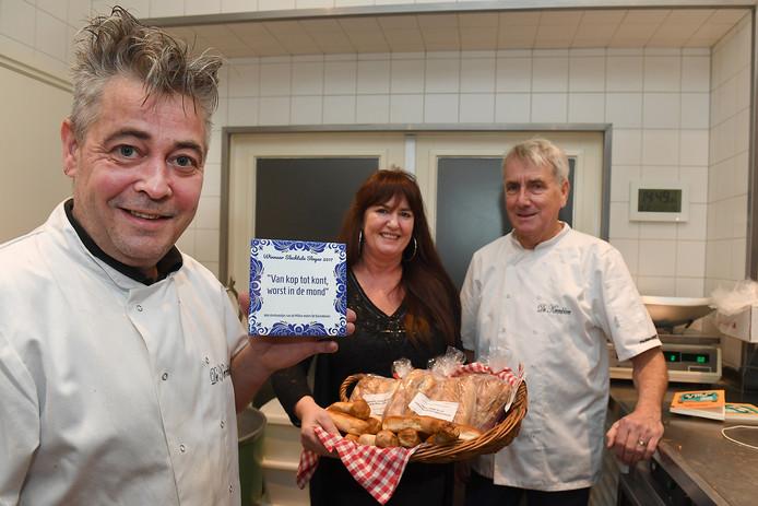 Millenaar Ramon Ligthart (links) met het gewonnen tegeltje voor de slechtste slogan van het jaar. Op de achtergrond zijn vriendin Tineke de Wit en oud-bakker André Leurs, die meehelpt met het maken van de worstenbroodjes.