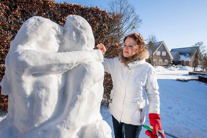 Kunstenares Louise Bramer terwijl ze werkt aan haar sneeuwbeeld 'Bevrijd van corona'.