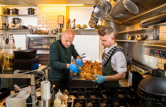 Eigenaar Joost  van de Braak (links) en chef-kok Rick Oostdijk zijn druk bezig met kippetjes, een van hun drie afhaal- en bezorggerechten.