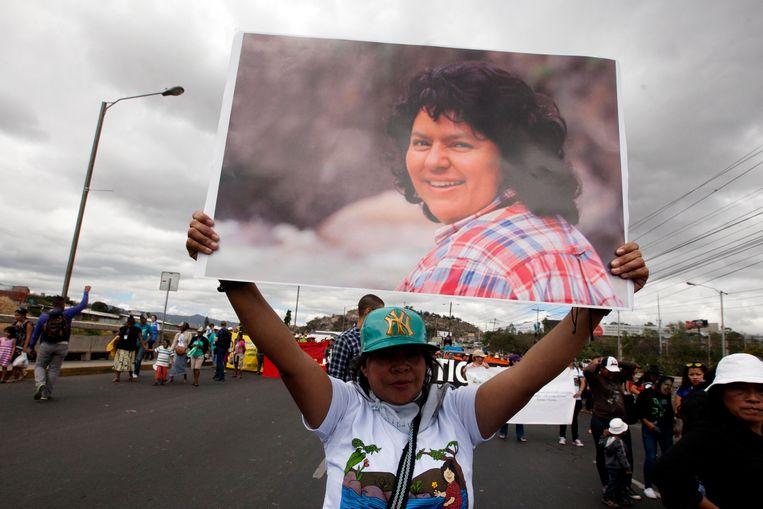 Een vrouw toont een foto van de vermoorde milieuactiviste Berta Cáceres tijdens een protestmars in Honduras. Beeld EFE