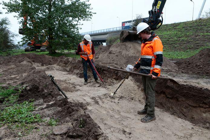 Bij het graven van de proefsleuf wordt steeds gekeken of er geen munitie is achtergebleven. Op de achtergrond is een deel van de Merwedebrug te zien.