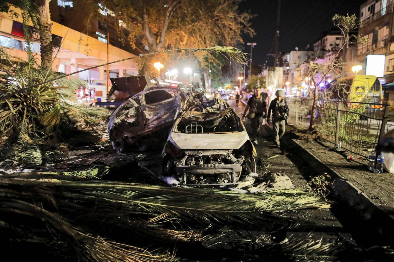 Israëlische soldaten lopen langs uitgebrande auto's in Holon, nabij Tel Aviv.  Beeld AFP