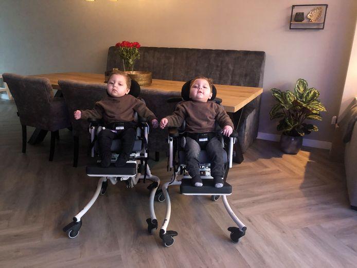 Damin en Ilay zittend in hun speciale rolstoelen, die niet meekunnen in de personenauto van het gezin.
