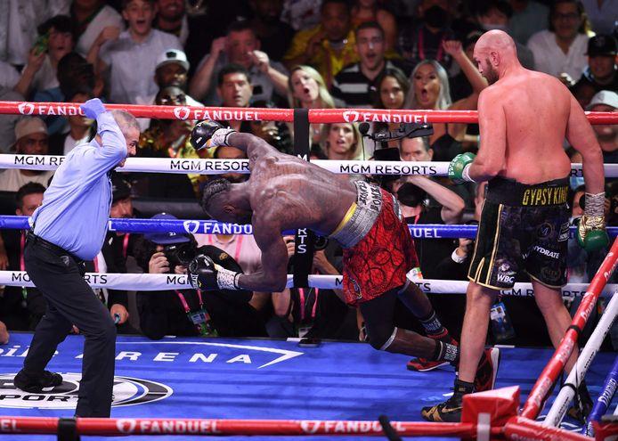 Deontay Wilder (m) gaat naar de grond en verliest de clash met Tyson Fury (r).