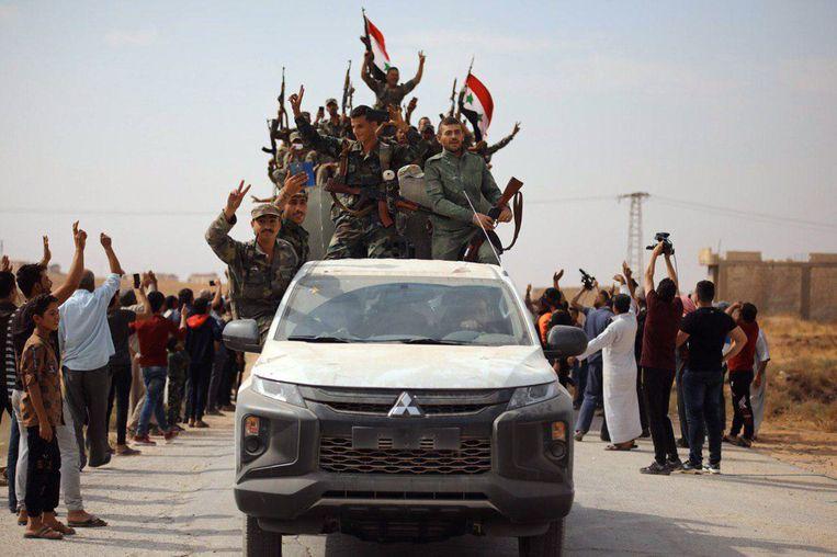 Syrische troepen worden toegejuicht wanneer ze de stad Ain Issa binnenrijden.  Beeld AFP