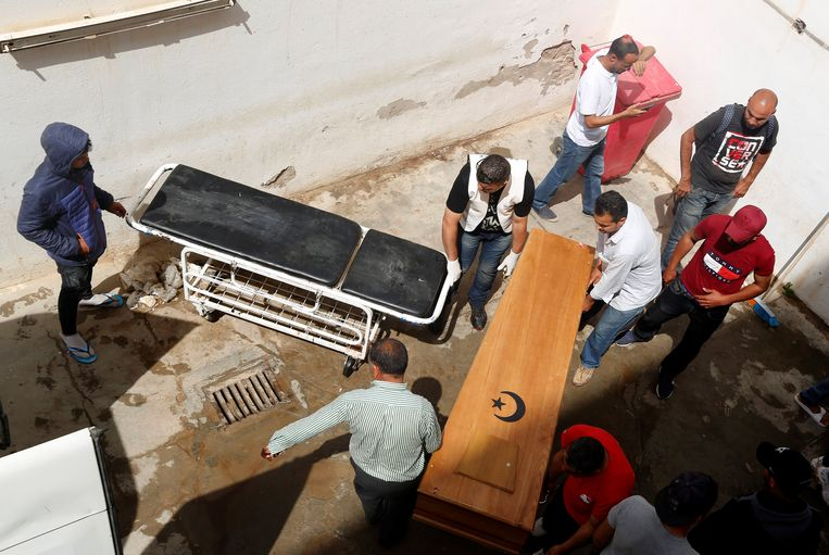 Enkele mannen dragen het lichaam van één van de overledenen weg. Beeld REUTERS