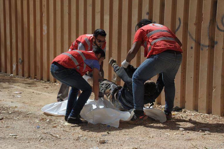 Medewerkers van het Rode Kruis halen een lichaam weg van een man die overleed bij gevechten in de Libische hoofdstad Benghazi Beeld afp