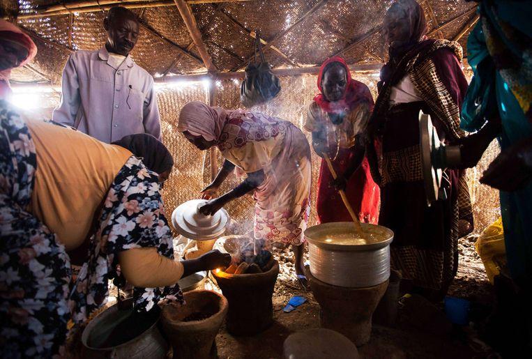 Nieuw geweld in de regio Darfur heeft duizenden mensen naar VN-vluchtelingenkampen gedreven. In totaal worden volgens persbureau AFP 40.000 mensen opgevangen in de kampen. De hulpmiddelen van de Verenigde Naties komen erdoor onder druk te staan volgens de organisatie. De volgende foto's zijn gemaakt in een kamp in Noord-Darfur. <br /><br />Hierboven: vrouwen koken in een voedseldistributiecentrum in een Rwandees kamp in Tawila, in het noorden van Soedan. Beeld AFP