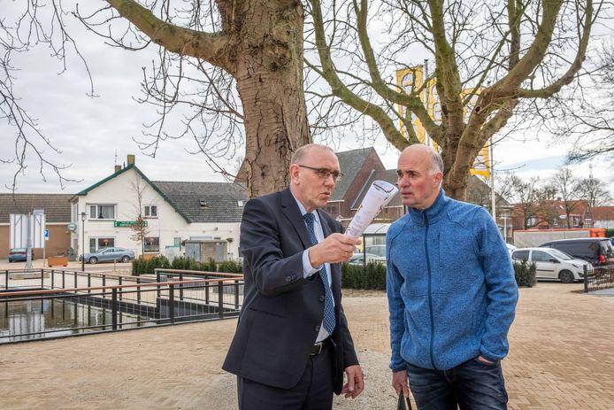 Oud-wethouder Jaap Sinke in het voorjaar van 2020 in gesprek met een Krabbendijkenaar over de net afgeronde herinrichting van het centrum. Op de achtergrond het nieuwe parkeerterrein waar Jumbo vlaggen en een stalling voor winkelwagentjes mocht neerzetten.