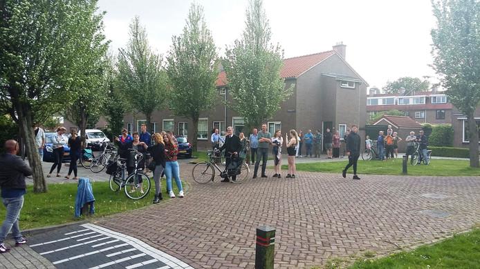 Belangstellenden stromen samen in de wijk waar de politie zoekt naar de mogelijke dader van de steekpartij.