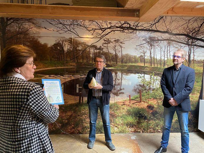 Voorzitter Wim Oltwater en penningmeester Maarten Jan Leppink van de Groene Waaier ontvangen het compliment van Water Natuurlijk uit handen van Ellen Pot van het Waterschap.