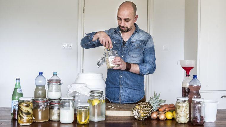 Kok Christian Weij bij zijn experimenteer-aanrecht vol gefermenteerde melk, groente en vruchten. Beeld Koen Verheijden