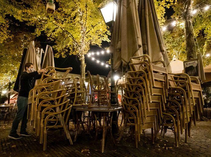 Het beeld van lege terrassen en gestapelde terrasstoelen op het Plein in Den Haag blijft nog wel even zo.