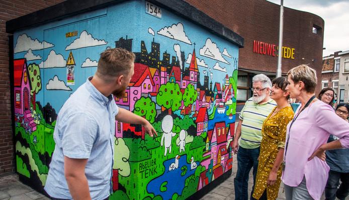 Kenny Jacobs (links) legt aan Frans van de Ven (van het wijkbestuur), Kim Pattiruhu en Aurora van Schijndel uit wat er op het trafohuisje staat.