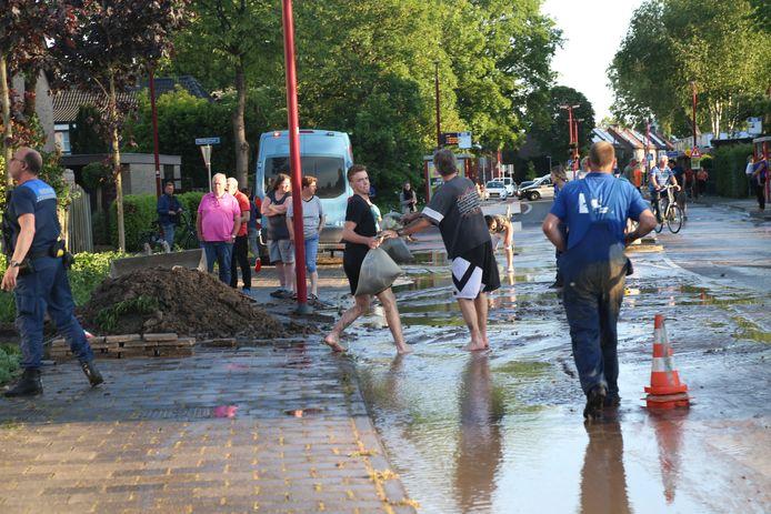Zandzakken werden gevuld om huizen in de buurt te beschermen tegen het water.