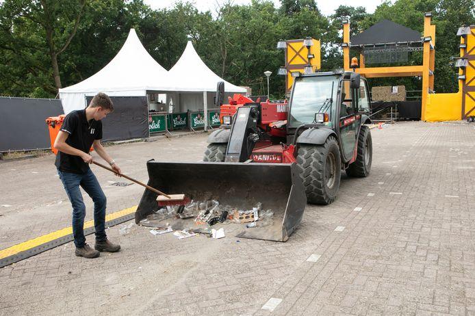 Een van de vrijwilligers ruimt zaterdag de boel op op het festivalterrein bij de Spartelvijver in Sibculo. Het Allermooiste Feestje mocht slechts een avond knallen