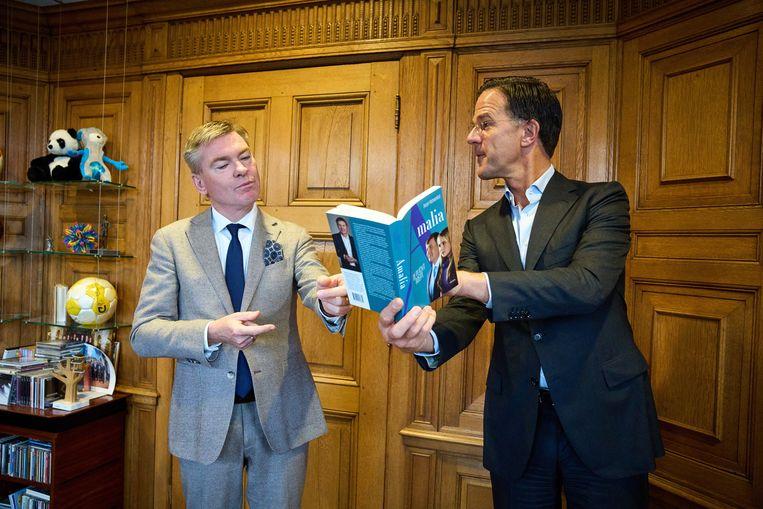 Peter Rehwinkel overhandigt in het Torentje het eerste exemplaar van zijn boek 'Amalia. De plicht roept' aan demissionair premier Mark Rutte. Beeld ANP
