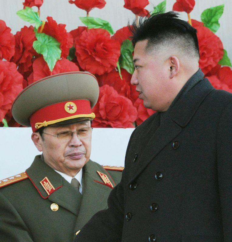 Kim Jong-un met op de achtergrond zijn oom Jang Song-taek, die eind 2013 is geëxecuteerd. Beeld ap