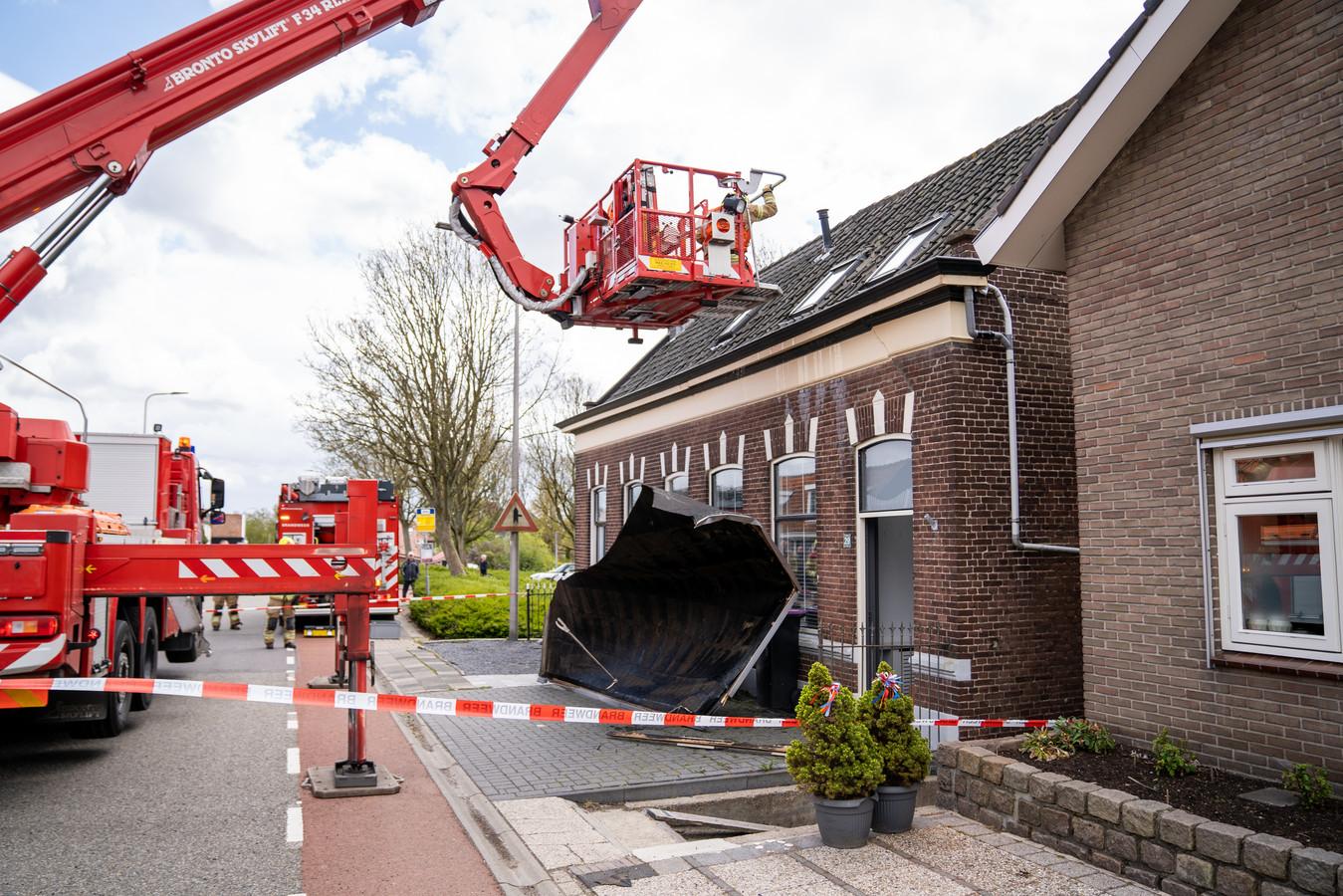 Met behulp van een hoogwerker heeft de brandweer het stuk dak in Zuidland veilig naar beneden gekregen.