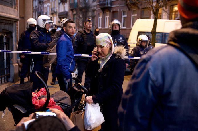 Een vrouw en haar baby gisteren bij de politieversperring tijdens de arrestatie van Salah Abdeslam in Molenbeek.