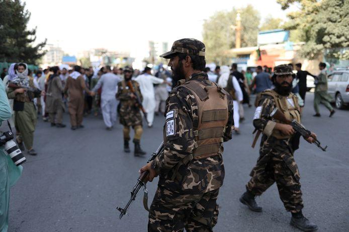 Talibansoldaten voor betogers in Kaboel.