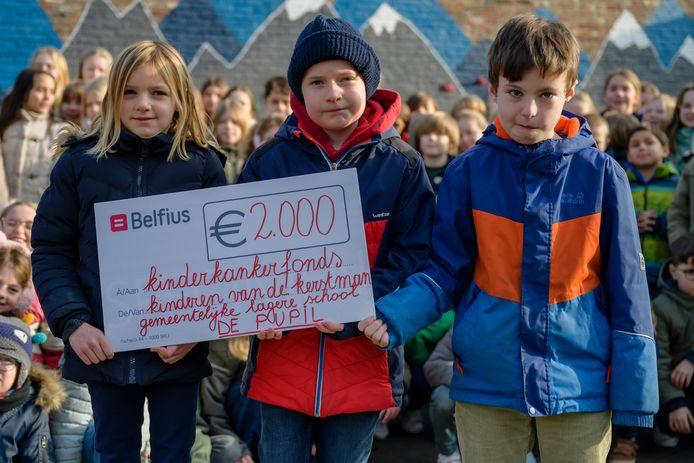Oskar (midden) mag een cheque van 2.000 euro overmaken aan het Kinderkankerfonds.